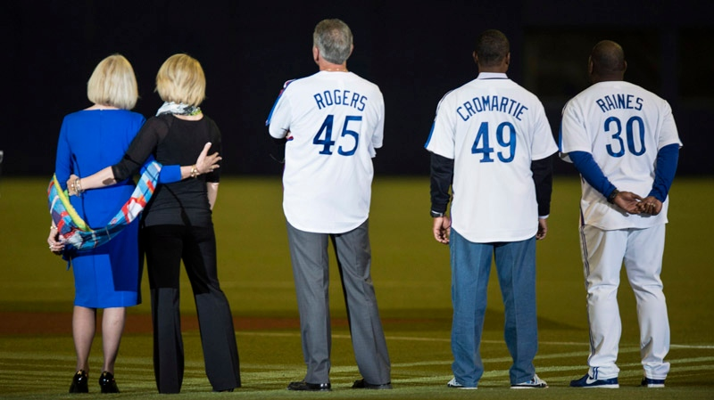 Sandy Carter, wife of former Montreal Expos Gary Carter, her daughter Kiimy, former Expos Steve Roger, Warren Cromartie and Tim Raines watch a video on the giant screen prior to a pre-season game between the Toronto Blue Jays and the New York Mets Friday, March 28, 2014 in Montreal. THE CANADIAN PRESS/Paul Chiasson
