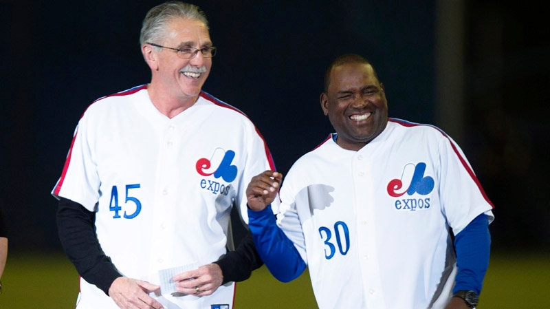 Former Montreal Expos Steve Rogers, left, and Tim Raines share a laugh during a ceremony prior to a pre-season game between the Toronto Blue Jays and the New York Mets Friday, March 28, 2014 in Montreal. (AP Photo/The Canadian Press, Paul Chiasson)