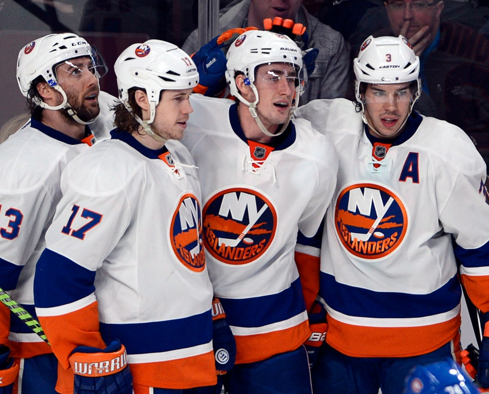 New York Islanders center Brock Nelson, 2nd right, celebrates with teammates Colin McDonald, left, Matt Martin (17) and New York Islanders defenseman Travis Hamonic (3) after scoring the second goal during second period NHL action against the Montreal Canadiens Thursday, April 10, 2014 in Montreal.THE CANADIAN PRESS/Ryan Remiorz
