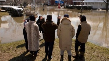 People look at a flooded street as the St. Francoi