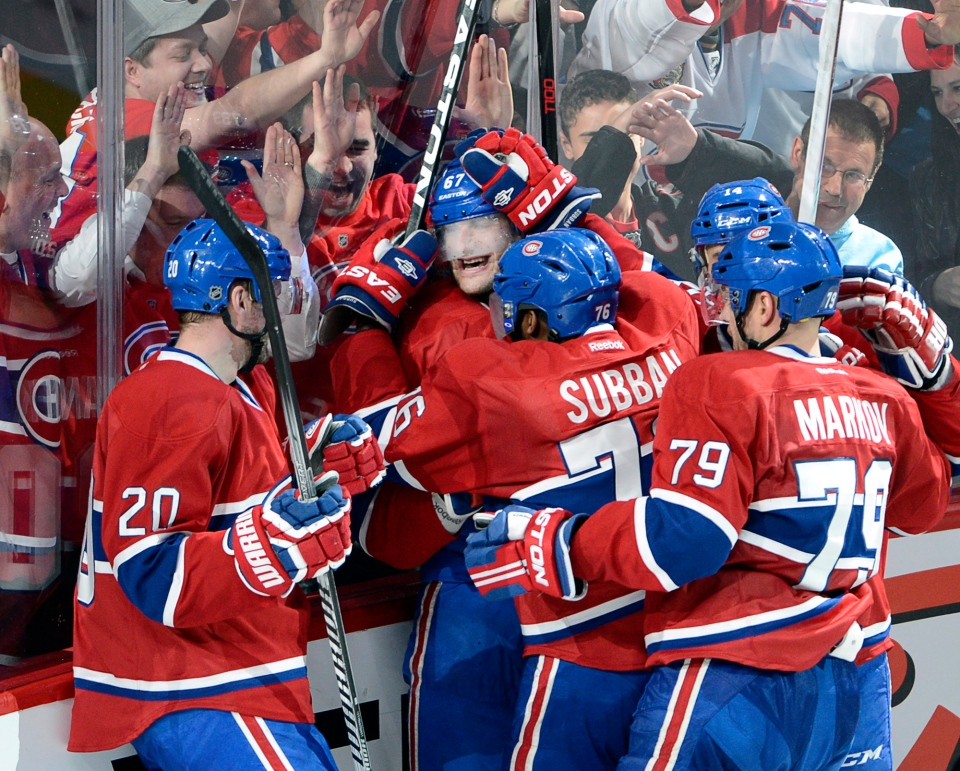 Montreal Canadiens left wing Max Pacioretty (67) is mobbed by teammates after scoring the winning goal against the Tampa Bay Lightning during third period National Hockey League Stanley Cup playoff action on Tuesday, April 22, 2014 in Montreal. THE CANADIAN PRESS/Ryan Remiorz