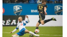 Montreal Impact's Marco Di Vaio, left, is brought