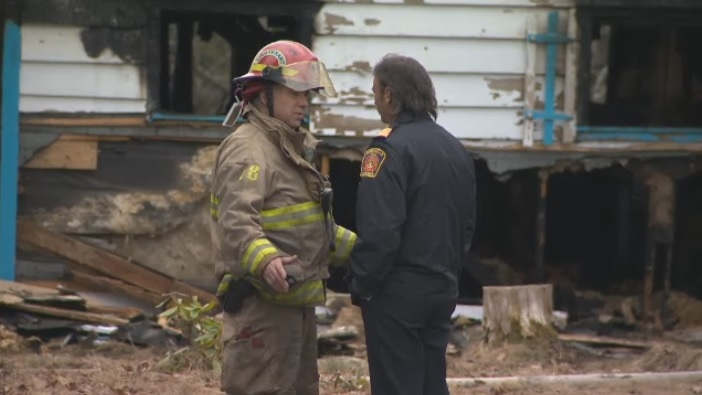 Firefighters at the scene of a house fire in Grenville sur la Rouge, 40 kilometres west of Lachute, Que. Sunday afternoon. A burned body was found in the house.