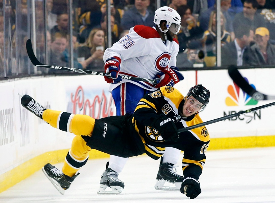 Boston Bruins right wing Reilly Smith (18) falls to the ice after crashing with Montreal Canadiens defenseman P.K. Subban (76) during the first period in Game 1 of an NHL hockey second-round playoff series in Boston, Thursday, May 1, 2014. (AP Photo/Elise Amendola)