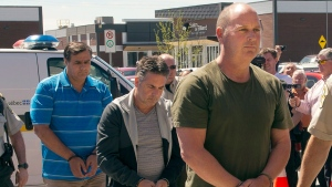 Former Montreal Maine and Atlantic Railway Ltd. employees Thomas Harding, right, Jean Demaitre, centre, and Richard Labrie are escorted by police to appear in court in Lac-Megantic, Que., on Tuesday, May 13, 2014. (Ryan Remiorz / THE CANADIAN PRESS)