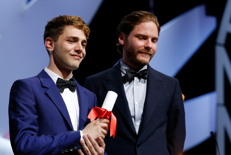 Actor Daniel Bruhl, right, stands alongside director Xavier Dolan after he presented him with the Jury Prize award for the film Mommy, which was shared with Jean-Luc Godard's Goodbye to Language (Adieu au langage) during the awards ceremony for the 67th international film festival, Cannes, southern France, Saturday, May 24, 2014. (AP / Alastair Grant)