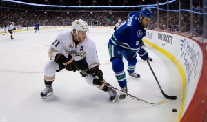 Vancouver Canucks' Zack Kassian, right, moves the puck along the boards as Anaheim Ducks' Saku Koivu, of Finland, defends during first period NHL hockey action in Vancouver, B.C., on Saturday March 29, 2014. (THE CANADIAN PRESS/Darryl Dyck)