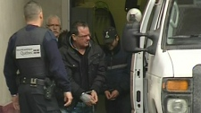 Raynald Desjardins, in handcuffs, exits a police van in Joliette (Dec. 21, 2011)