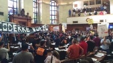 Protesters are seen inside council chambers Monday