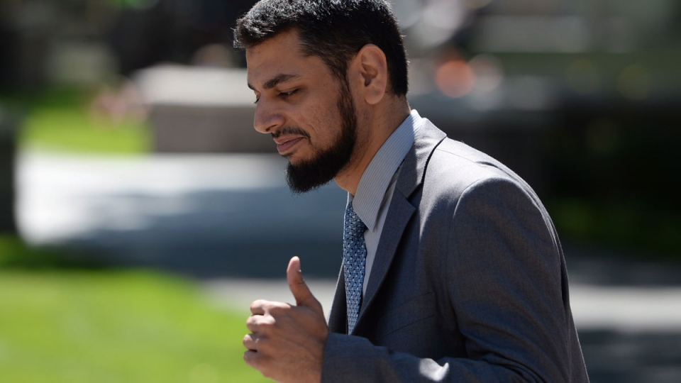 Khurram Syed Sher gives a thumbs up outside court in Ottawa on Tuesday, Aug. 19, 2014. (Sean Kilpatrick / THE CANADIAN PRESS)
