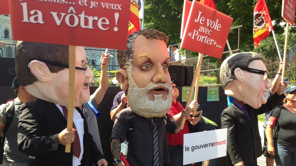 Protesters wearing giant heads of politicians such as Regis Labeaume, Denis Coderre and Premier Philippe Couillard protest in Quebec City as parliamentary hearings into pension reform begin on Aug. 20, 2014 (CTV Montreal/Pedro Querido)