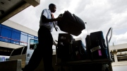 Baggage handler Mikaaill Heard loads luggage on May 21, 2008. (AP / Matt Rourke)