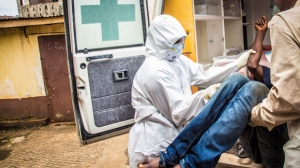 A health worker loads a suspected Ebola patient into the back of a ambulance in Freetown, Sierra Leone, Wednesday, Sept. 24, 2014. U.S. health officials laid out worst-case and best-case scenarios for the Ebola epidemic in West Africa, warning that the number of infected people could explode to at least 1.4 million by mid-January. (AP Photo/ Michael Duff)