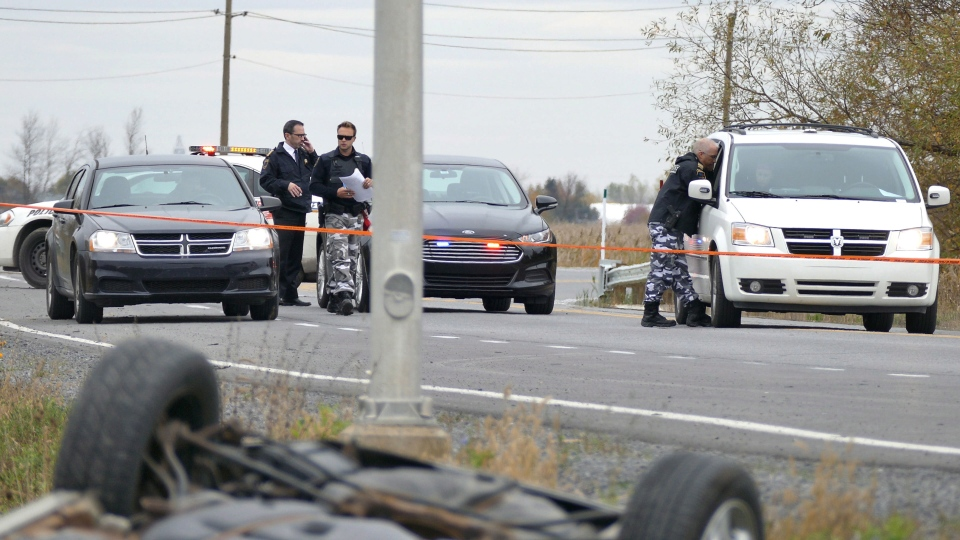 Investigators work at the scene near an overturned car in in St-Jean-sur-Richelieu on Monday, Oct. 20, 2014. (Pascal Marchand / THE CANADIAN PRESS)