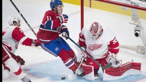 Montreal Canadiens' Brendan Gallagher, centre, slides in on Detroit Red Wings goaltender Jimmy Howard as Red Wing's Kyle Quincey, left, defends during second period NHL hockey action in Montreal, Tuesday, October 21, 2104. THE CANADIAN PRESS/Graham Hughes
