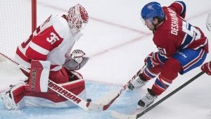 Montreal Canadiens' David Desharnais, right, slides in on Detroit Red Wings goaltender Jimmy Howard during third period NHL hockey action in Montreal, Tuesday, October 21, 2104. THE CANADIAN PRESS/Graham Hughes