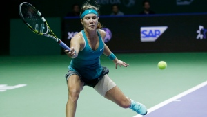 Canada's Eugenie Bouchard hits a forehand return to Serbia's Ana Ivanovic during their singles match at the WTA tennis finals in Singapore,Wednesday, Oct. 22, 2014. (AP Photo/Mark Baker)