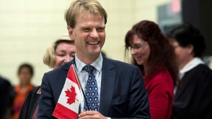 Chris Alexander, citizenship and immigration minister, holds a Canadian flag at a citizenship ceremony in Dartmouth, N.S. on Tuesday, October 14, 2014. (THE CANADIAN PRESS / Andrew Vaughan)