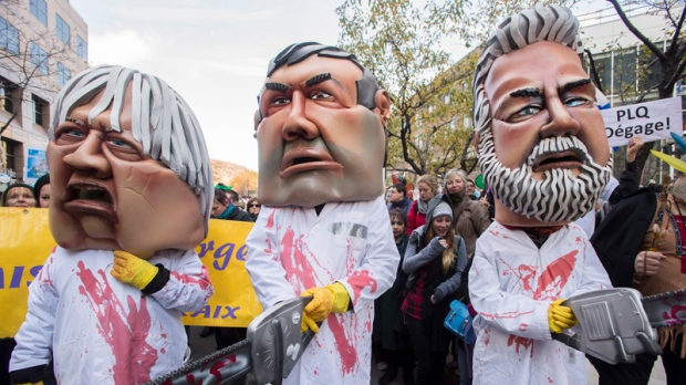 Protesters dressed as Quebec Premier Philippe Couillard, right, health minister Gaétan Barrette, left, and education minister Yves Bolduc take part in an anti-austerity demonstration in Montreal Friday, October 31, 2014. THE CANADIAN PRESS/Graham Hughes