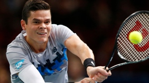 Milos Raonic of Canada returns the ball to Roger Federer of Switzerland during their quarterfinal match at the ATP World Tour Masters tennis tournament at Bercy stadium in Paris, France, Friday, Oct. 31, 2014. Raonic won 7-6, 7-5. (AP Photo/Michel Euler)