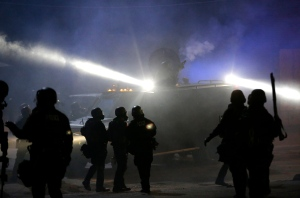 Police in riot gear stand around an armored vehicle as smoke fills the streets Tuesday, Nov. 25, 2014, in Ferguson, Mo. (AP / Charlie Riedel)