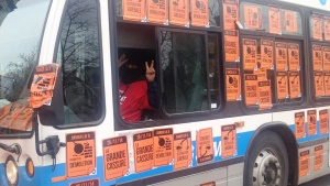 An STM driver wears a ski mask while driving a bus plastered with protest stickers (CTV Montreal/Maya Johnson)