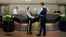 RCMP officers are shown in the lobby of SNC Lavalin in Montreal, Friday, April 13, 2012. (Graham Hughes / THE CANADIAN PRESS)