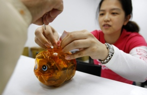 A campaign volunteer, right, helps a child add coins to a piggy bank in Banciao, Taiwan, in this Nov. 11, 2011 file photo. (AP / Wally Santana)