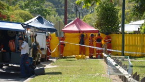 Emergency services workers cover off the perimeter fence of a house where eight children have been found dead in a Cairns suburb in far north Queensland, Australia, Friday, Dec. 19, 2014. (AP / Graeme Bint)