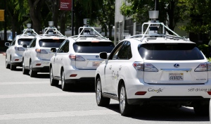 A row of Google self-driving cars are lined up outside the Computer History Museum in Mountain View, Calif., on Tuesday, May 13, 2014. (AP / Eric Risberg)