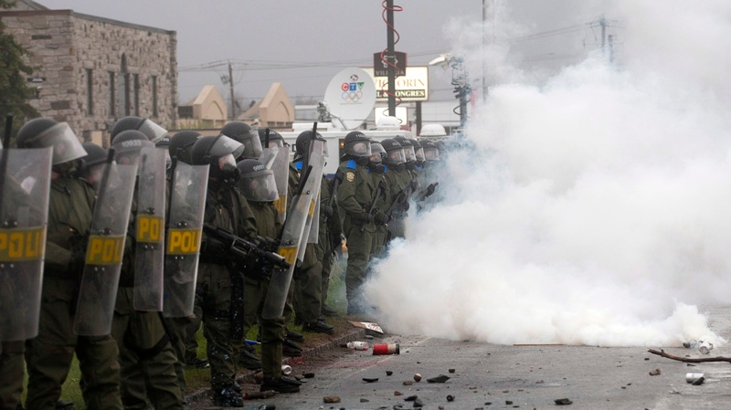 Riot police stand in a cloud of teargas, protecting a perimeter from riioters as the Quebec Liberal Party is meeting Friday, May 4, 2012 Victoriaville, Quebec. A violent standoff erupted on the streets of a small city where Quebec's governing party was holding its weekend convention, as protesters and provincial police rained physical abuse on each other Friday. THE CANADIAN PRESS/Jacques Boissinot