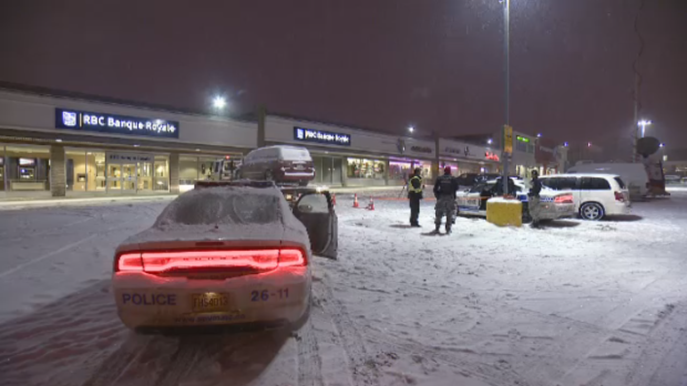 Montreal police survey the scene of a bank heist in Cote des Neiges Thursday, Jan. 29, 2015. Police say around 10:30 p.m., two masked, armed men walked into the bank, tied up the janitor and waited for the Garda truck to arrive.