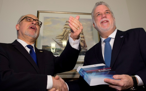 Quebec Finance Minister Carlos Leitao, left, gives a copy of the budget speech to Quebec Premier Philippe Couillard Thursday, March 26, 2015 at the premier's office in Quebec City. Leitao will table a provincial budget Thursday afternoon. THE CANADIAN PRESS/Jacques Boissinot