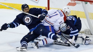 Winnipeg Jets' Dustin Byfuglien (33) and Montreal Canadiens' Brendan Gallagher (11) collide with Jets goaltender Ondrej Pavelec (31) after he makes the save during first period NHL action in Winnipeg on Thursday, March 26, 2015. THE CANADIAN PRESS/John Woods
