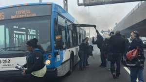 Passengers climb out of the bus after it pulled over on the Ville Marie Expressway Thursday, April 23. The bus eventually caught on fire. (Lauren Fagen)