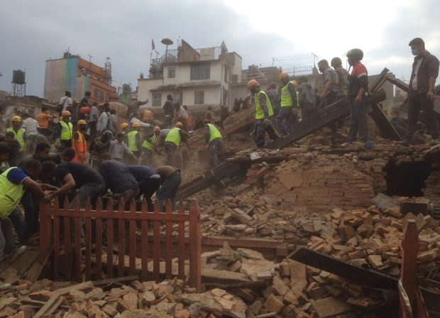 Rescuers clear the debris at Durbar Sqaure. A strong magnitude-7.9 earthquake shook Nepal's capital and the densely populated Kathmandu Valley before noon Saturday, causing extensive damage with toppled walls and collapsed buildings, officials said.  Saturday, April 25, 2015. (AP / Niranjan Shrestha)
