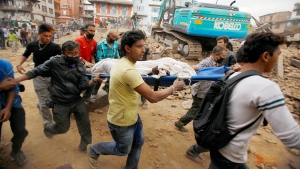Volunteers carry a victim on a stretcher, recovered from the debris of a building that collapsed after an earthquake in Kathmandu, Nepal, Saturday, April 25, 2015. (AP / Niranjan Shrestha)