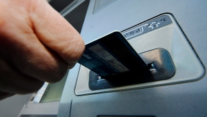 A person inserts a debit card into an ATM in Pittsburgh, Saturday, Jan. 5, 2013. (AP / Gene J. Puskar)