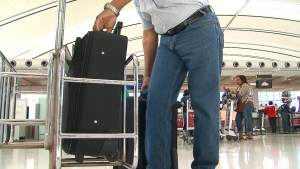 A passenger fits his luggage into a carry-on bag sizing device that may be used more often as Air Canada is set to begin cracking down on carry-on baggage.