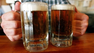 In this June 29, 2004 file photo, a bartender serves two mugs of beer at a tavern in Montpelier, Vt. (AP Photo/Toby Talbot, File)