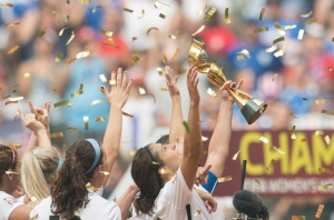 USA team members lift the trophy in celebration following their win over Japan at the final game soccer action at the FIFA Women's World Cup in Vancouver, B.C., on Sunday, July 5, 2015. (Jonathan Hayward / THE CANADIAN PRESS)