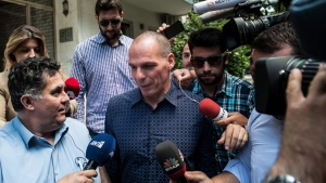 Outgoing Greek Finance Minister Yanis Varoufakis is surrounded by media as he leaves from his house in Athens, Monday, July 6, 2015. Varoufakis resigned Monday, saying he was told shortly after Greece's decisive referendum result that some other eurozone finance ministers and the country's other creditors would appreciate his not attending the ministers' meetings. (Giorgos Bampoukos/InTime News via AP)