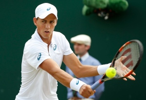 Vasek Pospisil of Canada returns a ball to Viktor Troicki of Serbia during their singles match at the All England Lawn Tennis Championships in Wimbledon, London, Monday July 6, 2015. (AP / Alastair Grant)