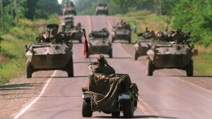 A Mohawk Warrior sits in golf cart and uses binoculars to view approaching Canadian army armoured vehiches on Highway 344 on the Kanesatake Reserve at Oka, Que., September 1, 1990. (Tom Hanson / THE CANADIAN PRESS)