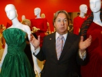 In this Oct. 10, 2002 file photo, fashion designer Arnold Scaasi talks about his designs at the Fashion Institute of Technology in New York. Scaasi, whose flamboyant creations adorned first ladies, movie stars and socialites, died Tuesday, Aug. 4, 2015, at New York-Presbyterian Hospital of cardiac arrest. He was 85. (AP / Suzanne Plunkett, File)