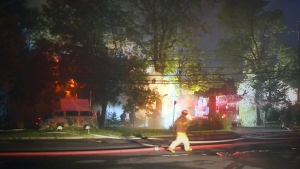 Café d'ailleurs is engulfed in flames as a firefighter walks past on Aug. 5, 2015 (CTV Montreal/Cosmo Santamaria)