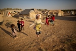 In this Sunday, July 19, 2015 file photo, Syrian refugee girl, Zubaida Faisal, 10, skips a rope while she and other children play near their tents at an informal tented settlement near the Syrian border on the outskirts of Mafraq, Jordan. (AP/Muhammed Muheisen)