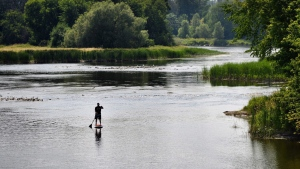A man makes his way down the Rideau River on a standup paddleboard in Ottawa on Monday, July 13, 2015. (Sean Kilpatrick / THE CANADIAN PRESS)