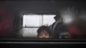 A Syrian refugee child looks out of a bus that will take him and his family to the center for asylum seekers near Roszke, southern Hungary, Friday, Sept. 11, 2015.  (AP / Muhammed Muheisen)