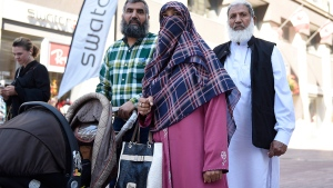 Zunera Ishaq, centre, leaves the Federal Court of Appeal after it overturned a ban on the wearing niqabs at citizenship ceremonies, in Ottawa on Tuesday, Sept. 15, 2015. (Justin Tang / THE CANADIAN PRESS)